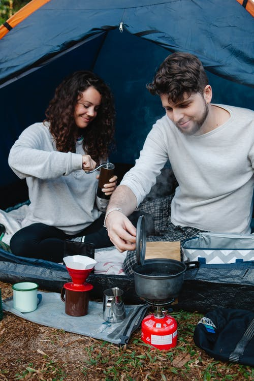 Young content male traveler heating water in pot on burner stove of portable gas bottle near girlfriend grinding coffee during trip