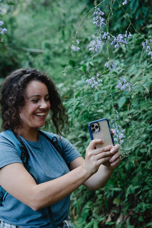 Lächelnde Frau Im Blauen Rundhalsausschnitt T Shirt, Das Iphone Hält