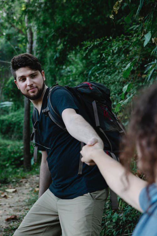 Backpacker holding hand of crop beloved in forest