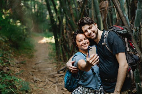 Cheerful young couple in casual clothes and backpacks cuddling and smiling while taking selfie on mobile phone during trekking in green forest