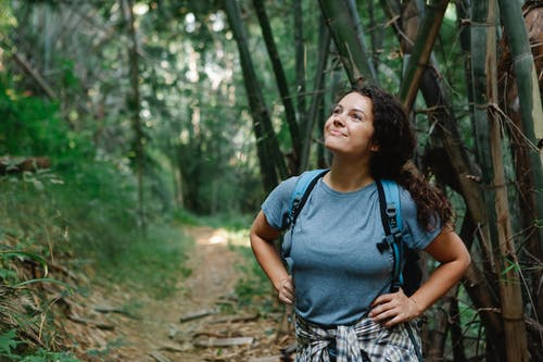 Positive young female traveler admiring nature standing on path in forest