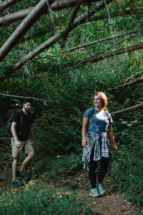 Full body of active young couple in casual clothes and backpacks smiling while walking on narrow pathway in lush green forest during trekking