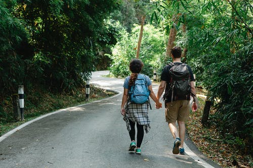 Anonymous couple holding hands while strolling on road in woods