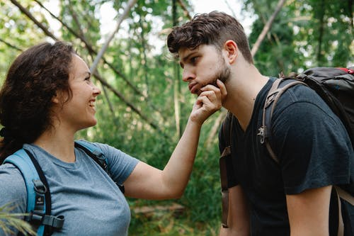 Side view of happy young woman smiling and touching face of tired boyfriend making grimace while standing together in green forest during hiking trip