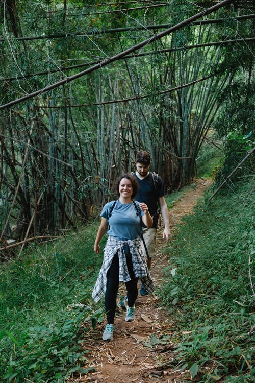 Content young couple hiking in tropical rainforest during summer holidays