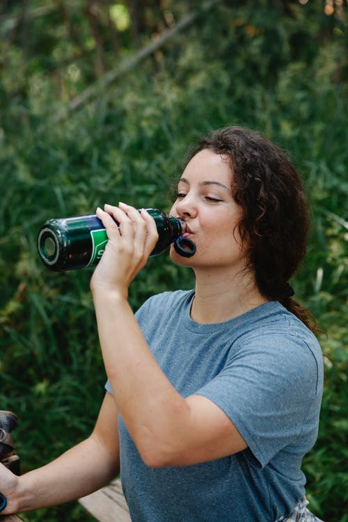 Tired young woman drinking water during hiking trip in forest