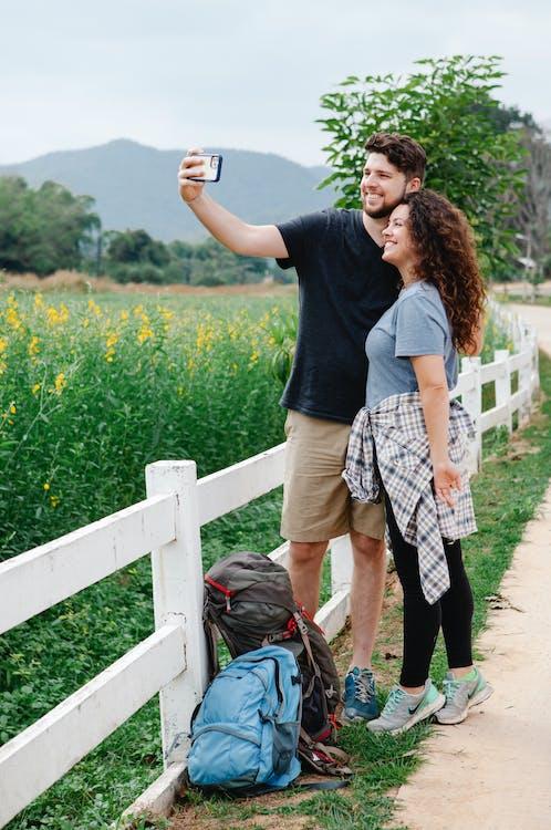 Happy couple taking selfie standing near green meadow in mountainous countryside