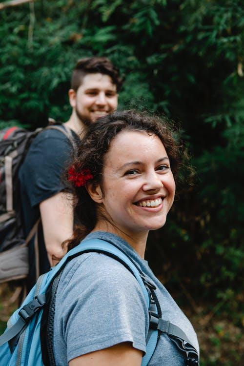 Cheerful young couple smiling at camera during hiking in woods