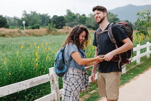 男人和女人在綠草地上行走時手牽著手