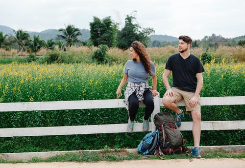 Couple of tourists sitting on fence near field with plants