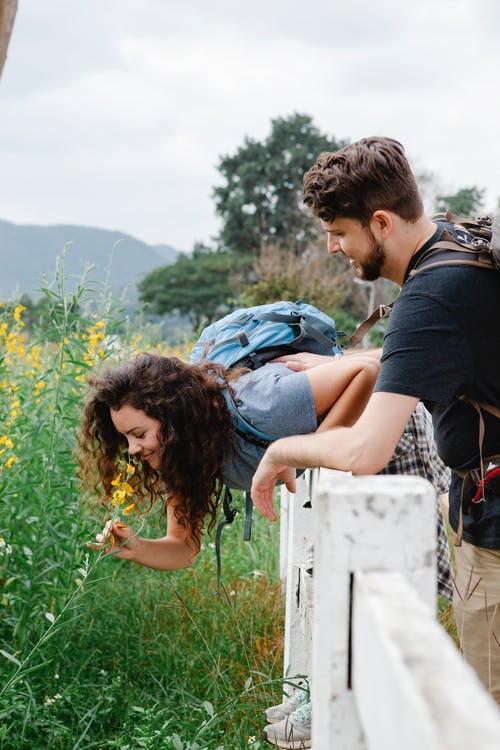 Side view of positive young couple of travelers in casual outfits with backpacks standing on wooden fence near green grassy meadow with flowers near trees and mountains in summer day