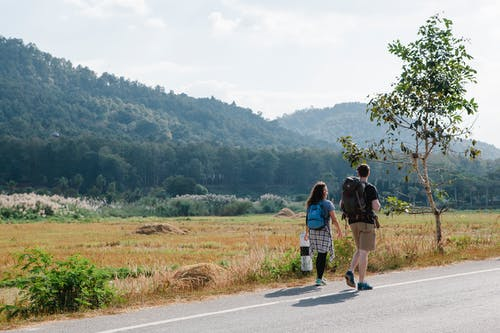 Anonymous couple of tourists walking on road near grassy meadow