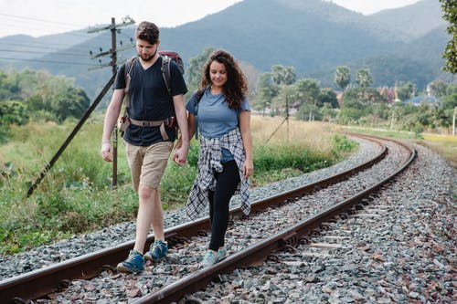 Cheerful couple of travelers in casual clothes with backpacks holding hands and  walking along railway placed in countryside against green mountains in daytime
