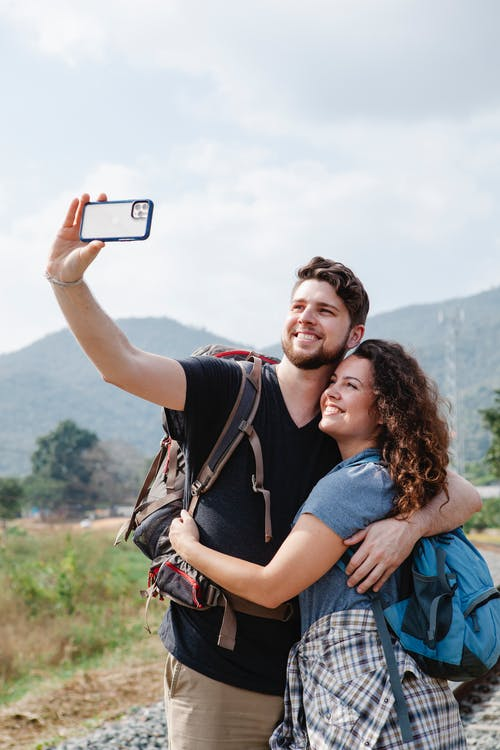 Happy couple of hikers in casual clothes with backpacks hugging and taking selfie on smartphone in nature against mountains in sunny day