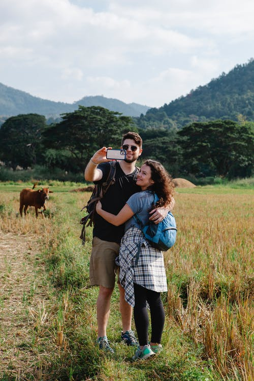 Full body of cheerful couple of hikers embracing and taking selfie on smartphone in field with pasturing cows against hills in sunny day
