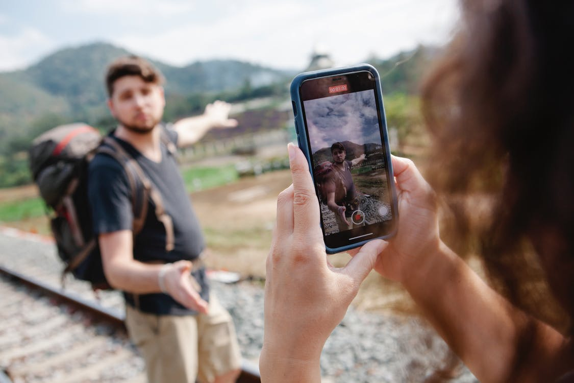 Female taking video of traveler during hike in countryside in daylight