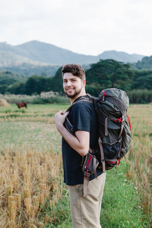 Content hiker in casual clothes with backpack standing in field against green hills and looking at camera in daylight