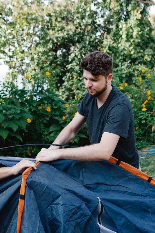 Hiker pitching tent in nature in daytime