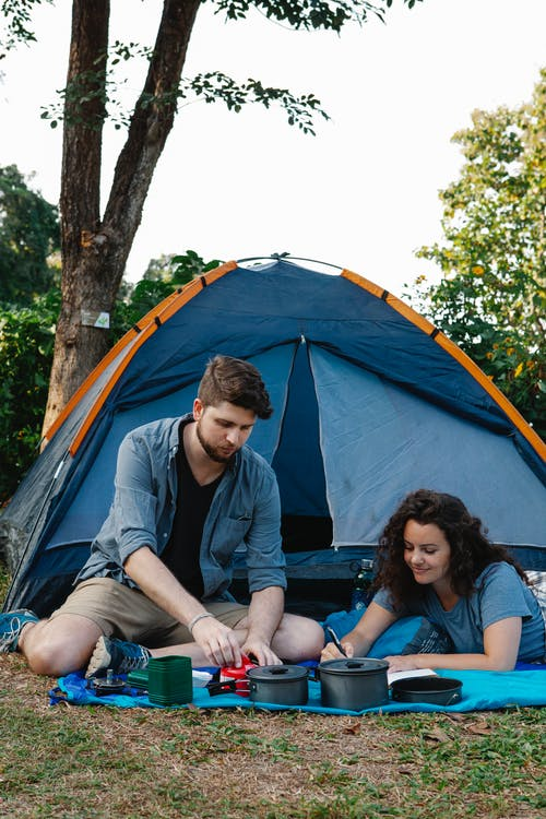 Content young couple resting on plaid near camping tent in nature
