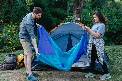 Traveling couple spreading blanket during camping in nature