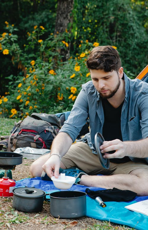 Young man preparing food during picnic after hiking trip in forest