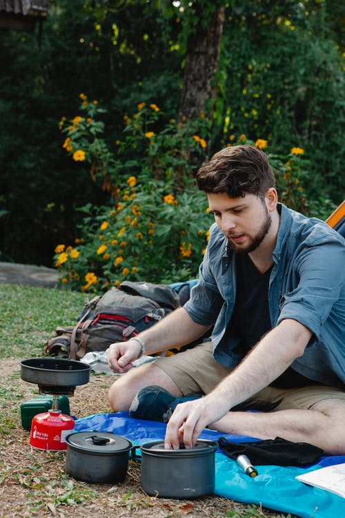 Young male traveler preparing food at campsite in nature