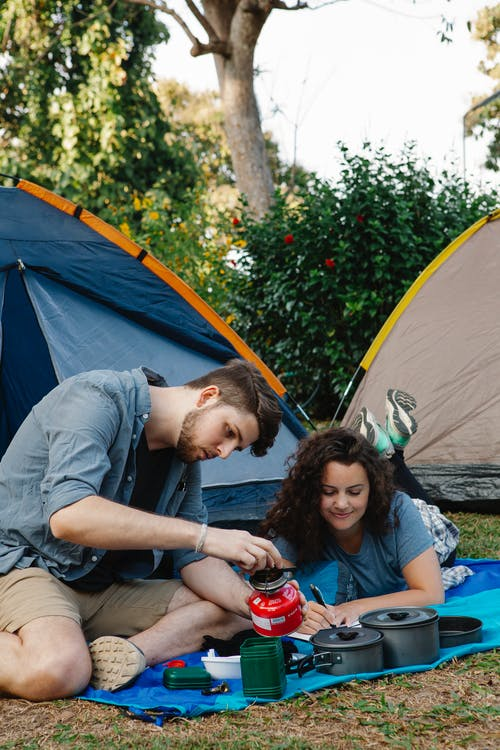 Concentrated young male hiker in casual clothes switching on portable gas stove while sitting near tent with girlfriend during camping in green woods