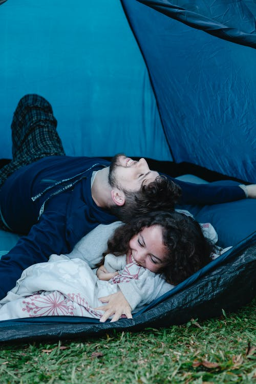 Cheerful young male traveler smiling and lying on happy girlfriend while having fun together in camping tent