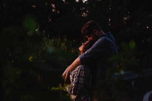 Loving young couple embracing in forest at sunset
