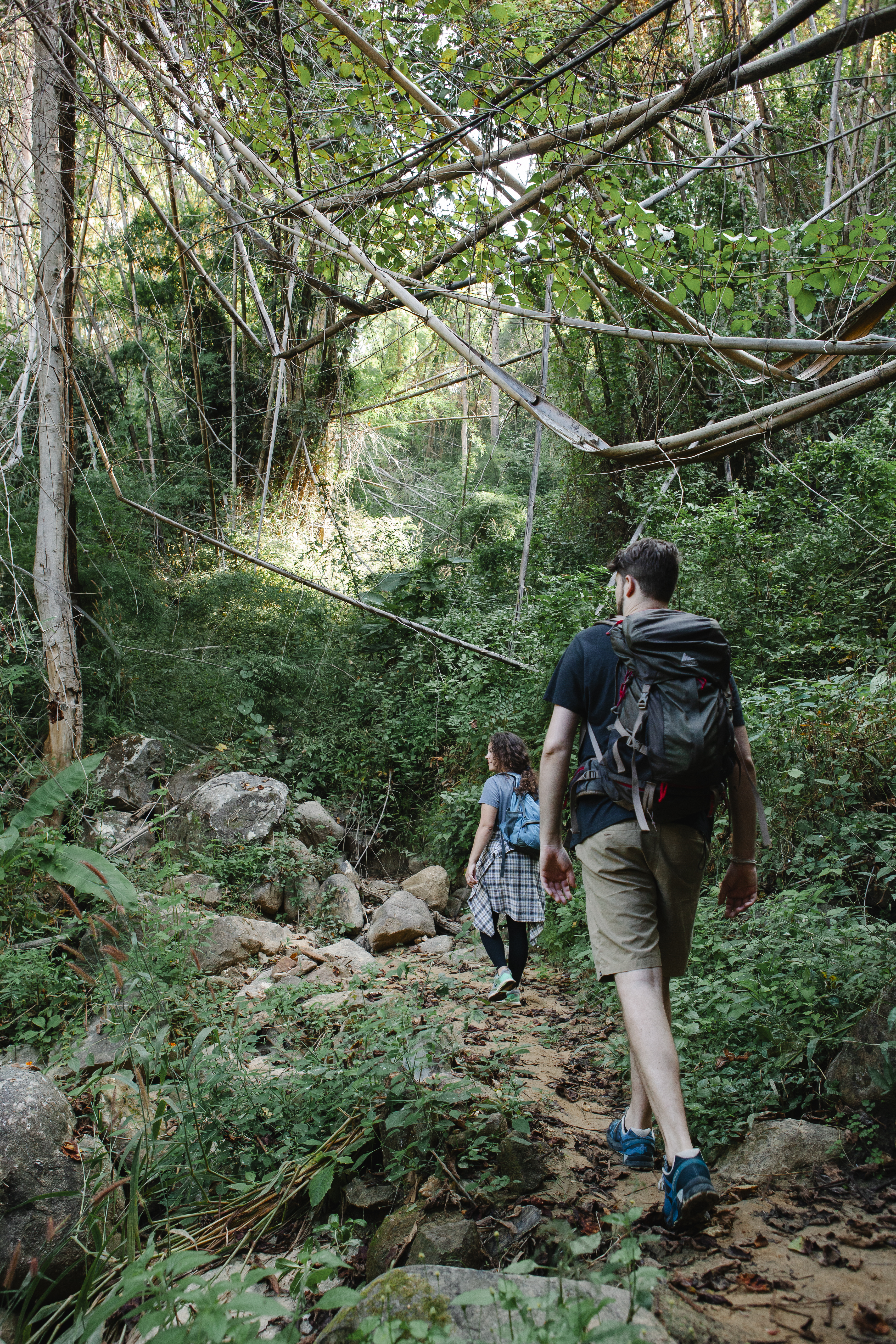 traveling young couple walking on rough path in forest