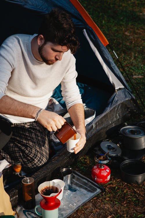 Calm young man pouring coffee in camping tent