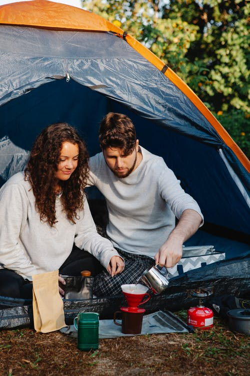 Romantic young couple resting in tent and preparing pour over coffee at campsite in sunny morning