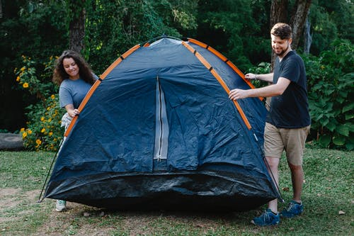 Happy couple of travelers in casual clothes pitching tent on green grass in forest during hike in daytime