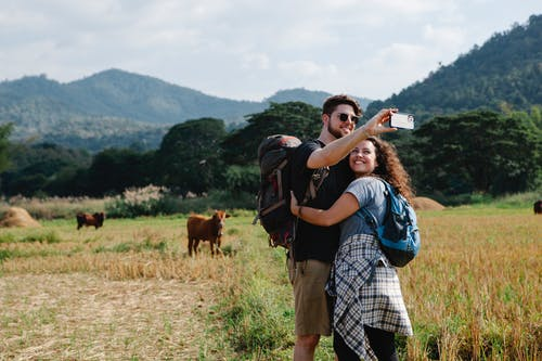 Happy couple of travelers hugging and taking selfie in field against hills
