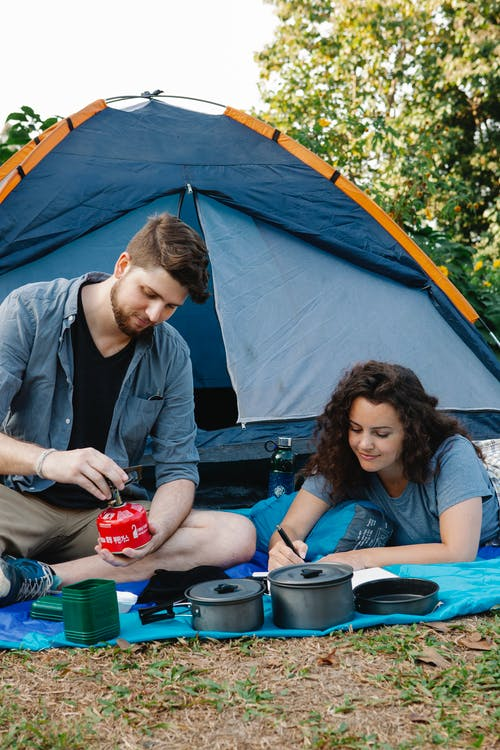 Couple of hikers sitting on grass and preparing food while spending time in nature with tent in sunny day