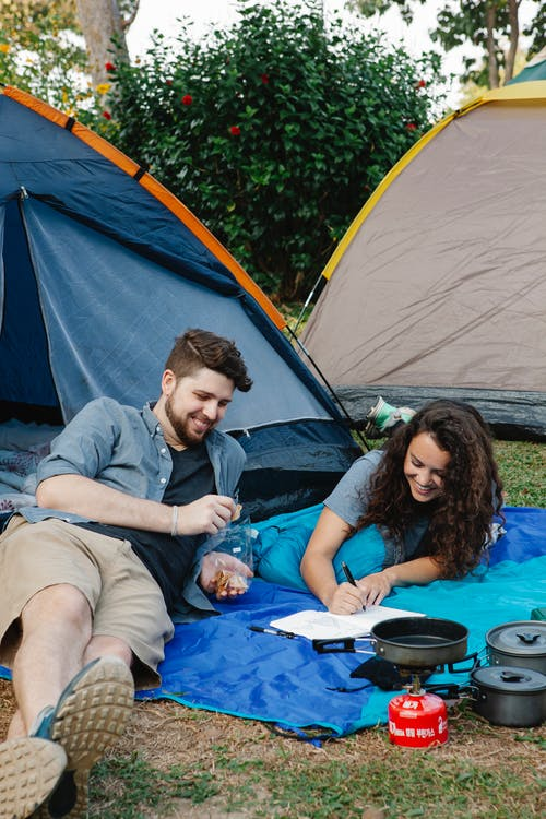 Couple of hiker lying near tents in nature in daytime