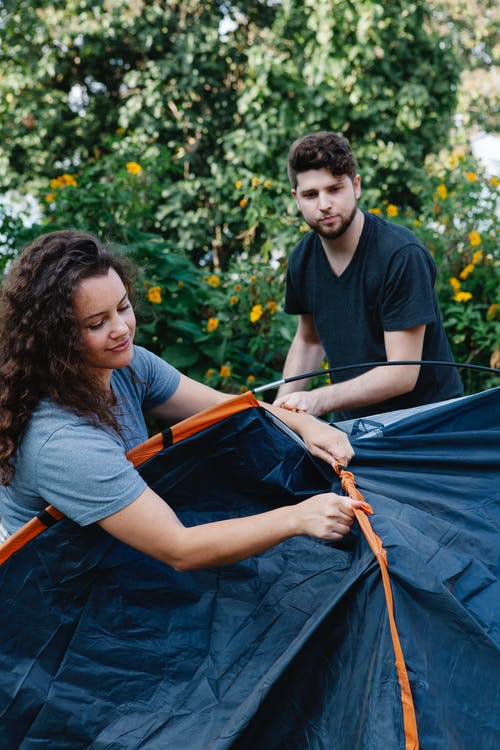 Couple of hikers pitching tent in green forest in daytime