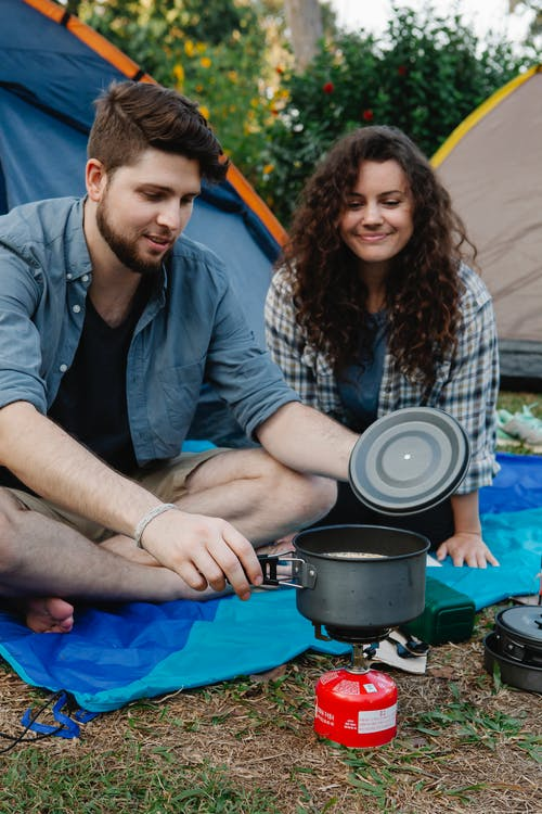 Positive couple of hikers in casual clothes sitting on ground near tents and preparing food in pot while traveling in nature