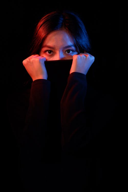 Pensive Asian female covering face with sweater and looking at camera