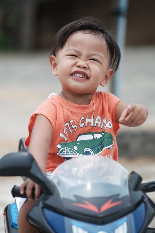 Cheerful Asian toddler in summer outfit sitting on scooter while pointing at camera