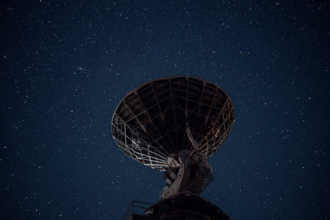 Radio telescope under bright starry sky
