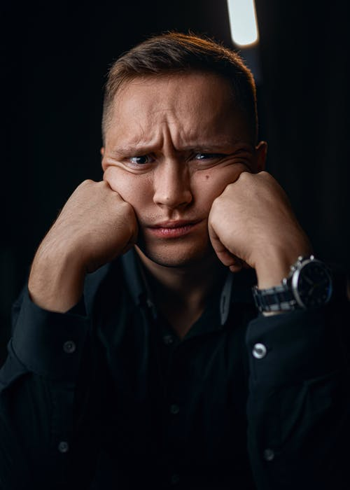 Unhappy male in formal outfit with wristwatch leaning on fists while looking at camera