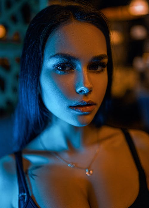 Charming dark haired female with light makeup and tattoo standing under illumination and looking at camera