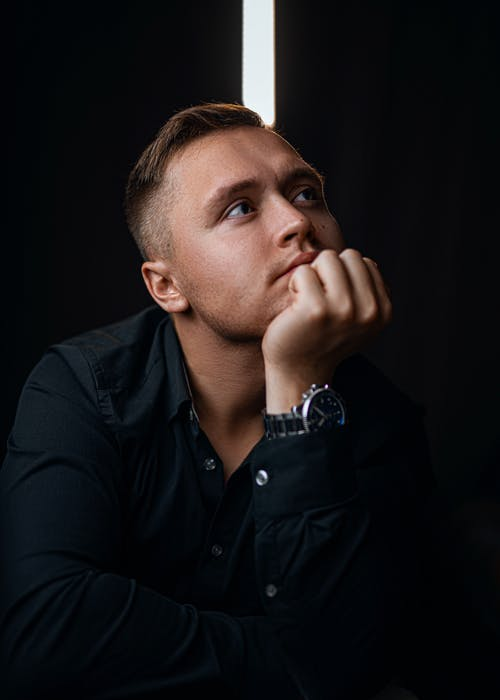 Pensive young male with wristwatch in formal wear touching chin while sitting in dark room and looking away