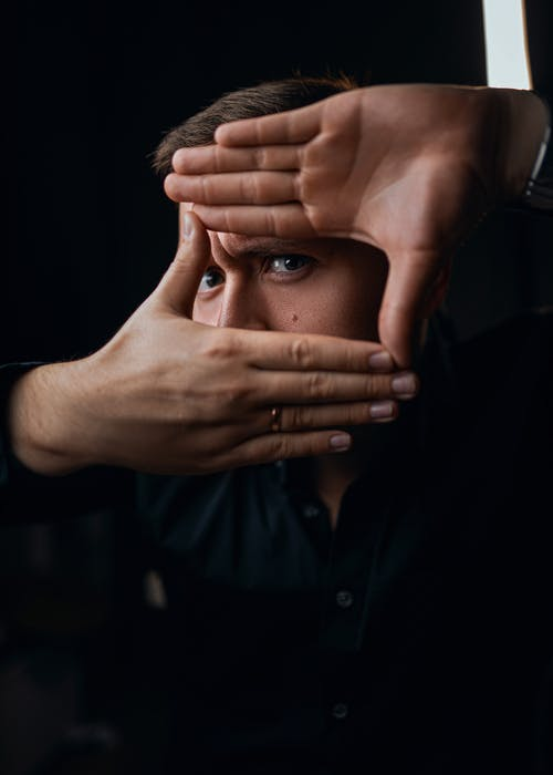 Frowning male with ring covering face with hand while standing in dark room and looking at camera