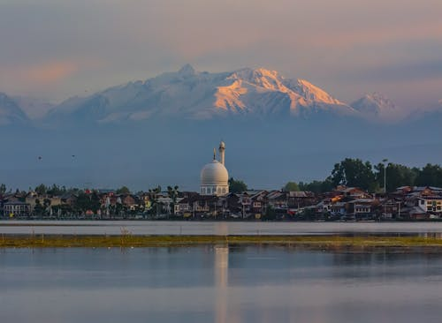 Picturesque scenery of residential building with Muslim place of worship on shore of lake in highland
