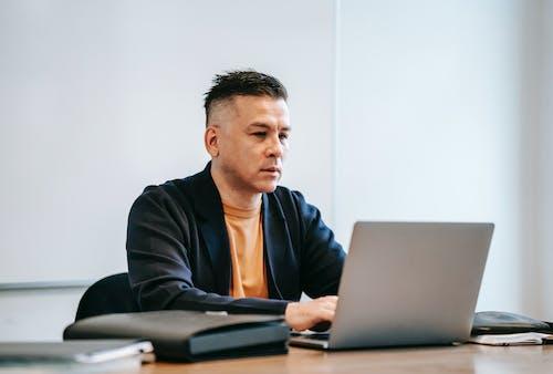 Man In Black Blazer Menggunakan Macbook Pro