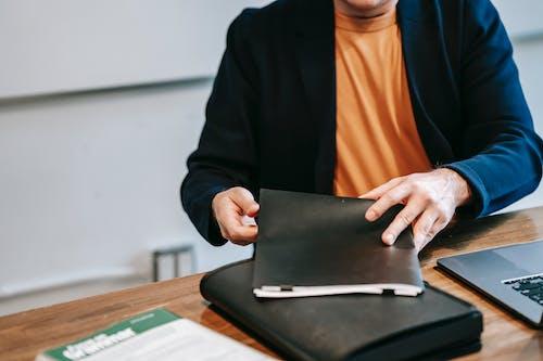 Frau Im Orangefarbenen Hemd Und Im Schwarzen Blazer, Der Schwarzen Laptop Computer Hält