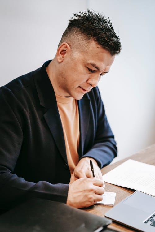 Photo Of Man Writing On A Piece Of Paper