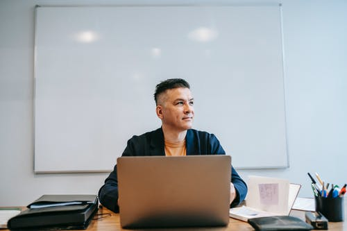 Pria Dengan Kaos Polo Hitam Duduk Di Depan Komputer Laptop Coklat